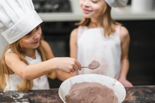 Uśmiechnięci rodzeństwa w kuchni jest ubranym szefa kuchni kapelusz bierze łyżkę kakaowy proszek