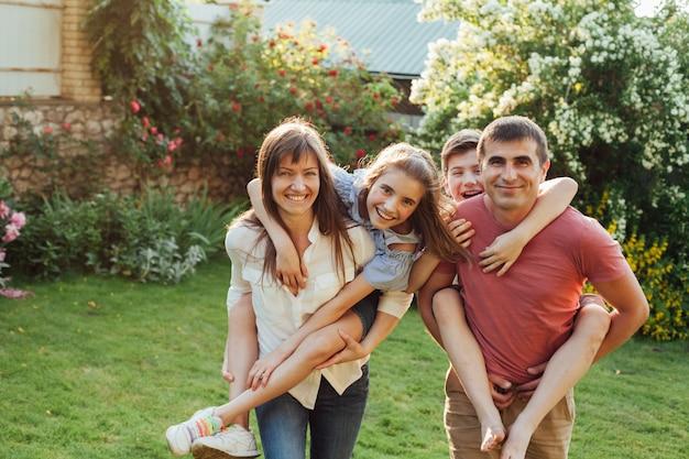 Uśmiechnięci rodzice dając przejażdżkę piggyback swoim dzieciom w parku