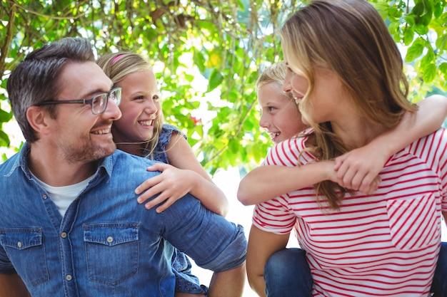 Uśmiechnięci rodzice daje piggyback dzieciom