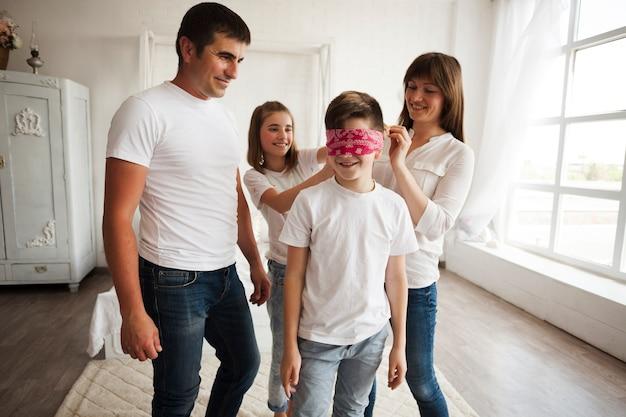 Uśmiechnięci rodzice patrząc na swoją córkę wiążącą szalik w oczach brata