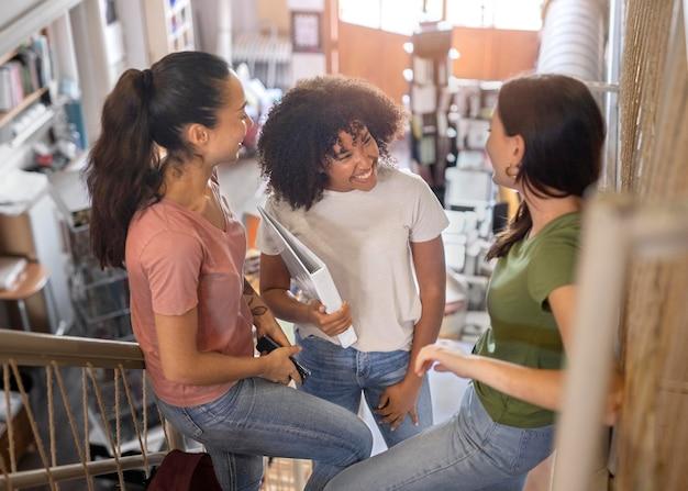 Uśmiechnięci studenci rozmawiający o średnim ujęciu