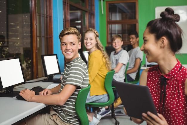 Uśmiechnięci studenci studiujący na cyfrowym tablecie i komputerze w klasie