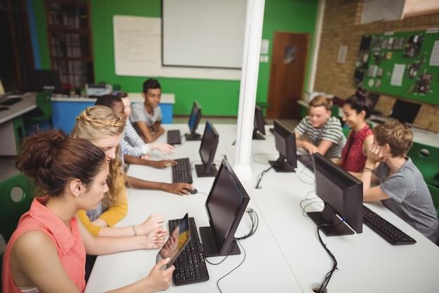 Uśmiechnięci studenci studiujący w sali komputerowej
