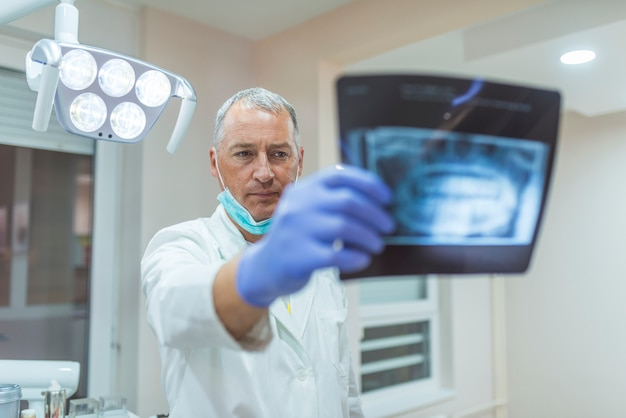 Uśmiechnięci szczęśliwi dentysta trzyma promieniowania rentgenowskie.