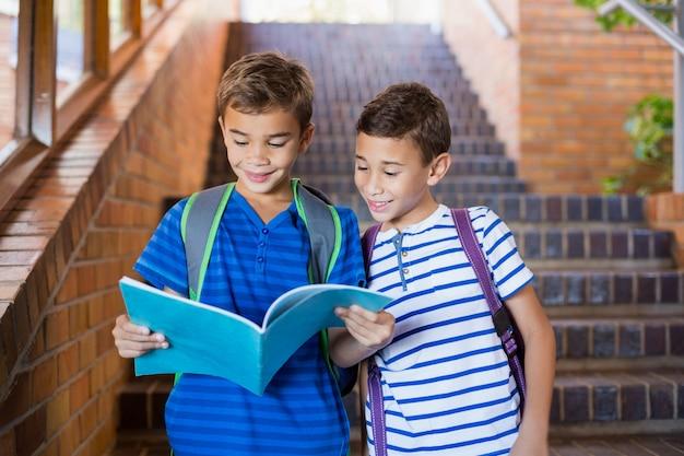 Uśmiechnięci szkolni dzieciaki czyta książkę na schody
