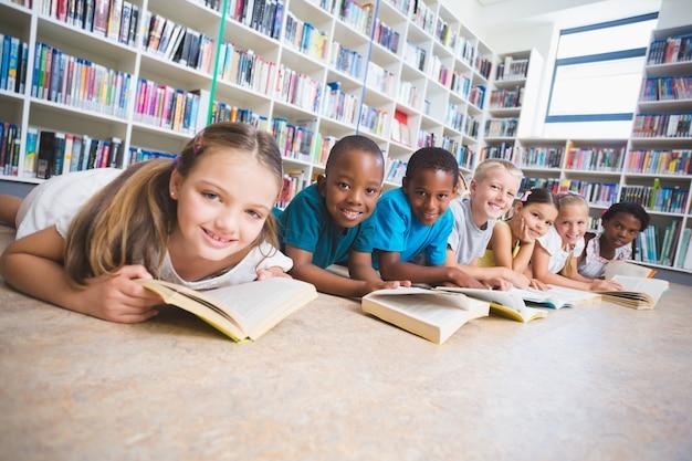 Uśmiechnięci szkolni dzieciaki kłama na podłogowej czytelniczej książce w bibliotece