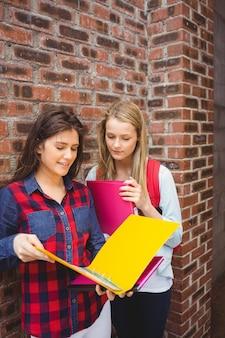 Uśmiechnięci ucznie czyta książkę przy uniwersytetem