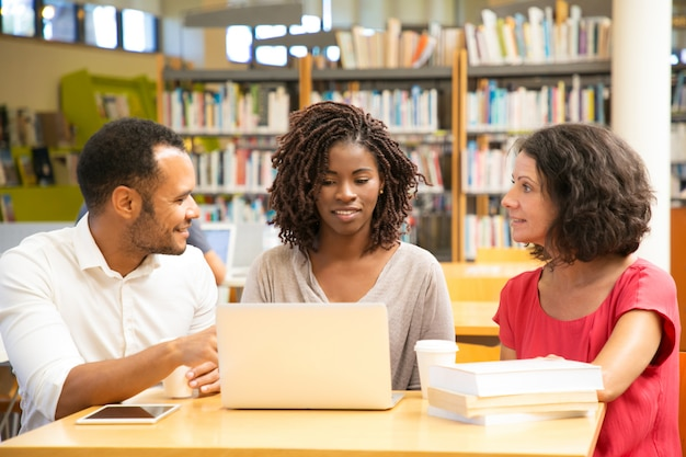 Uśmiechnięci ucznie dyskutuje coś podczas gdy pracujący z laptopem