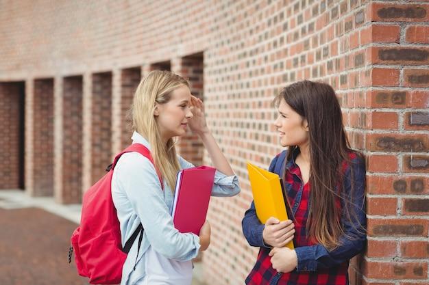 Uśmiechnięci ucznie opowiada plenerowego przy uniwersytetem