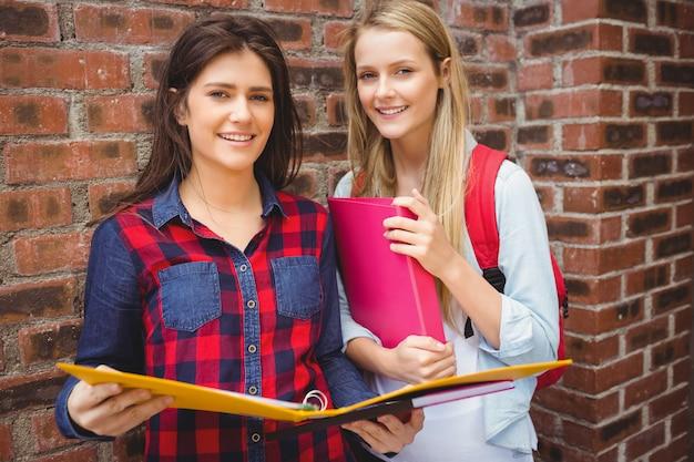 Uśmiechnięci ucznie patrzeje kamerę przy uniwersytetem z segregatorem