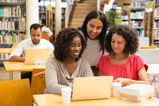 Uśmiechnięci ucznie pracuje z laptopem przy biblioteką