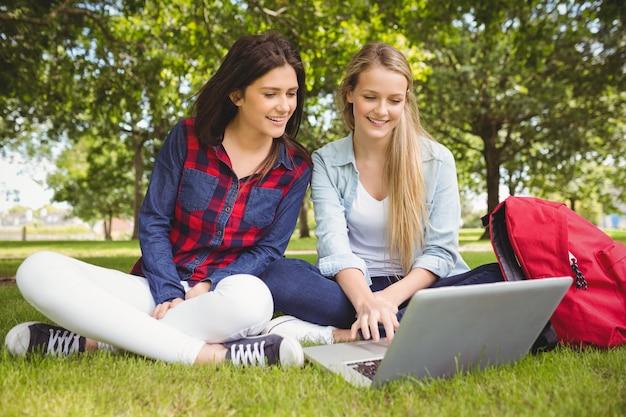 Uśmiechnięci ucznie używa laptop przy parkiem