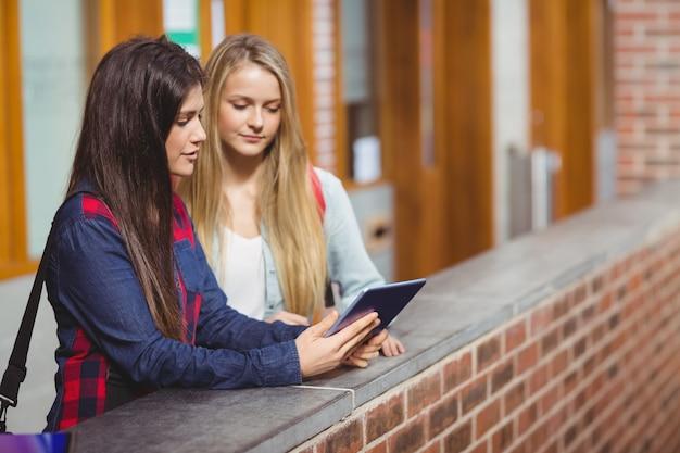 Uśmiechnięci ucznie używa pastylkę wpólnie na uniwersytecie