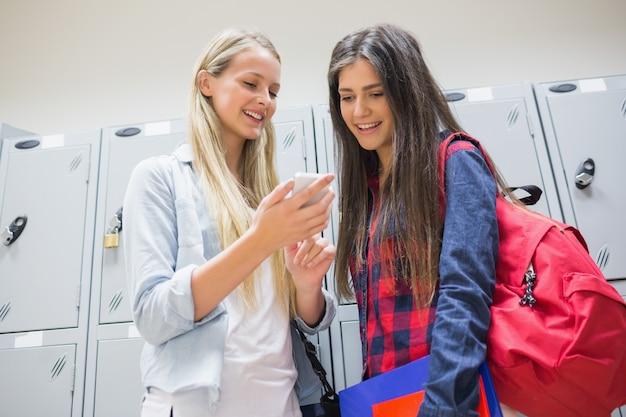 Uśmiechnięci ucznie używa smartphone blisko szafek przy uniwersytetem