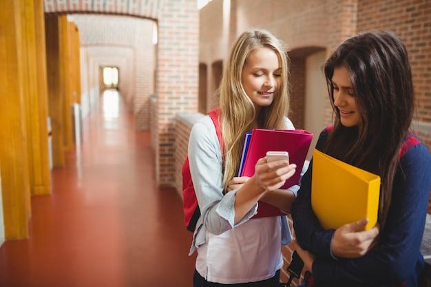 Uśmiechnięci ucznie używa smartphone przy uniwersytetem