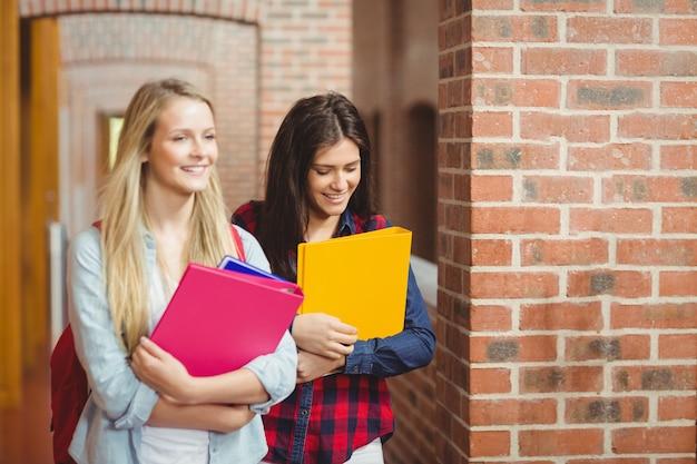 Uśmiechnięci ucznie z książkami w korytarzu przy uniwersytetem