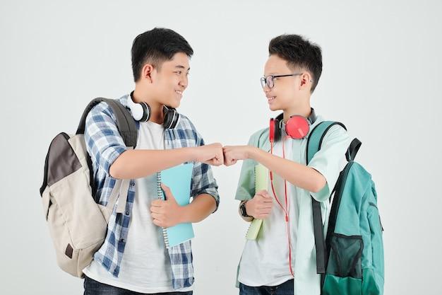 Uśmiechnięci uczniowie robią uderzenie pięścią, pokazując kciuki do góry i patrząc na siebie