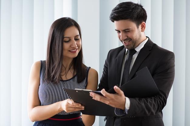 Uśmiechnięci ufni koledzy egzamininuje dokument wpólnie