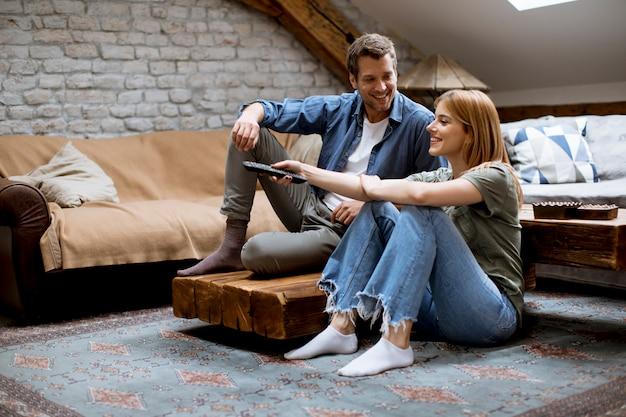 Uśmiechnięci urocza potomstwo para relaksuje tv w domu i ogląda