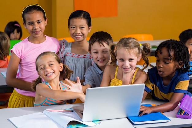Uśmiechnięci wielo- etniczni dzieci używa laptop