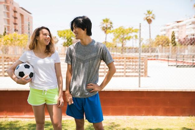 Uśmiechnięci wieloetniczni nastolatkowie patrzeje each inny w miastowym tle