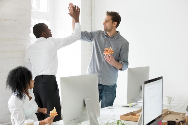 Uśmiechnięci wielorasowi coworkers daje wysokości pięć łasowania pizzy wpólnie przy biurem