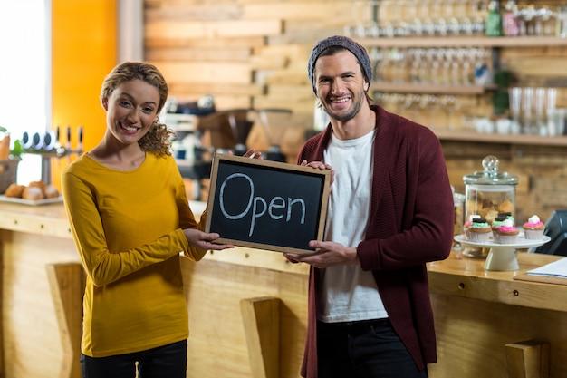 Uśmiechnięci właściciele stoi z otwartym znakiem wsiadają w kawiarni