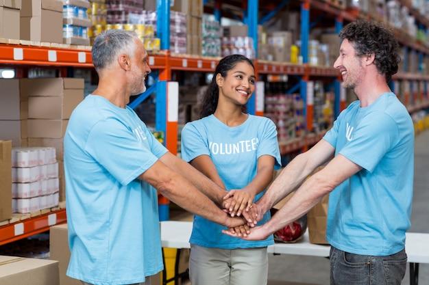 Uśmiechnięci wolontariusze łączą ręce i patrzą na siebie