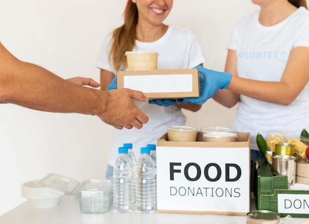 Uśmiechnięci wolontariusze w rękawiczkach przekazują pudełka z jedzeniem do darowizny