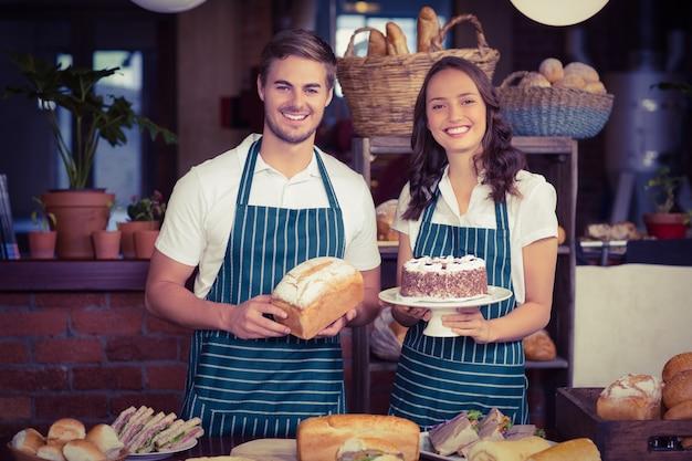 Uśmiechnięci współpracownicy pokazuje chleb i tort