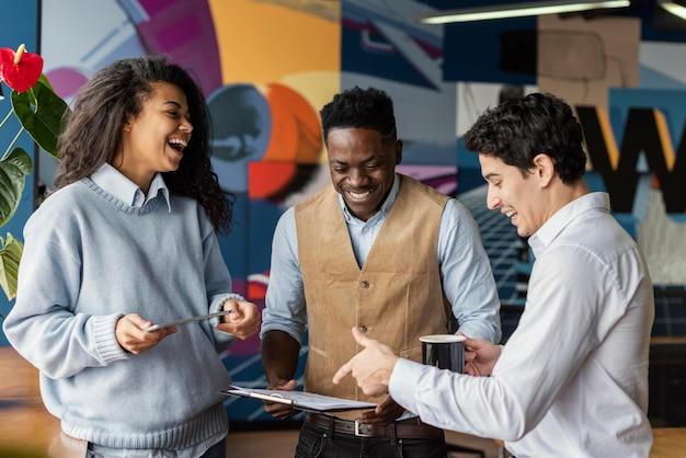 Uśmiechnięci współpracownicy w biurze rozmawiają