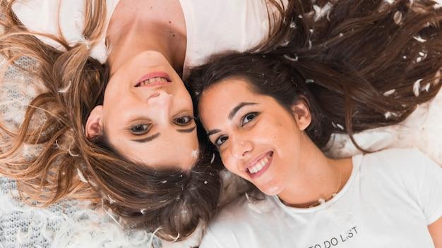 Uśmiechnięci żeńscy przyjaciele kłama na piórkach