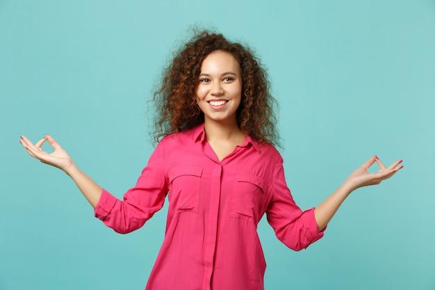 Uśmiechnięta african american dziewczyna w ubranie trzymaj się za ręce w geście jogi, relaksując medytację na białym tle na niebieskim tle turkusu. ludzie szczere emocje, koncepcja stylu życia. makieta miejsca na kopię.