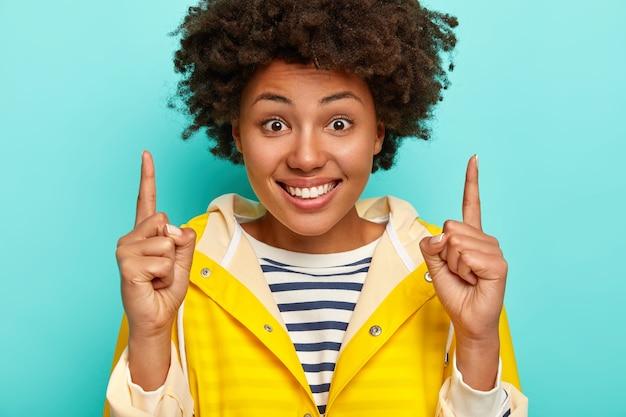 Uśmiechnięta afro american kobieta z radosnym wyrazem twarzy, pokazuje kierunek powyżej, nosi sweter w paski i żółty płaszcz przeciwdeszczowy, odizolowany na niebieskim tle.