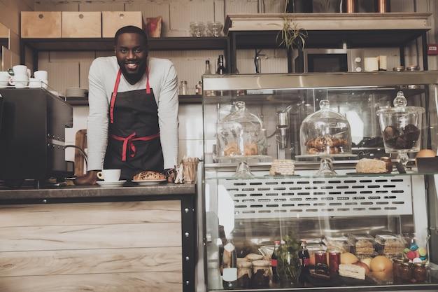 Uśmiechnięta afro amerykańska barista samiec przy pracą