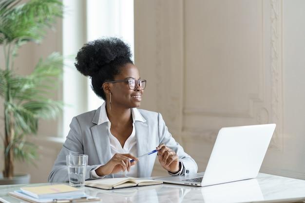 Uśmiechnięta afro kobieta w marynarce nosić okulary pracy na komputerze w domowym biurze, odwracając się.