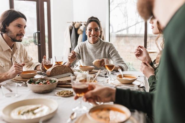 Uśmiechnięta afroamerykanin kobieta o ciemnych kręconych włosach siedzi przy stole rozmarzonym jedzeniem zupy z kromką chleba w ręku