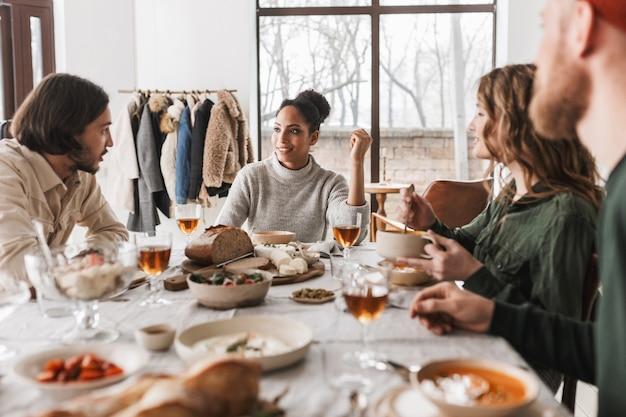 Uśmiechnięta afroamerykanin kobieta z ciemnymi kręconymi włosami siedzi przy stole rozmawiając z kolegami marzycielsko