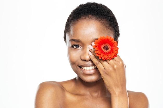 Uśmiechnięta afroamerykańska kobieta pozuje z kwiatem na białym tle