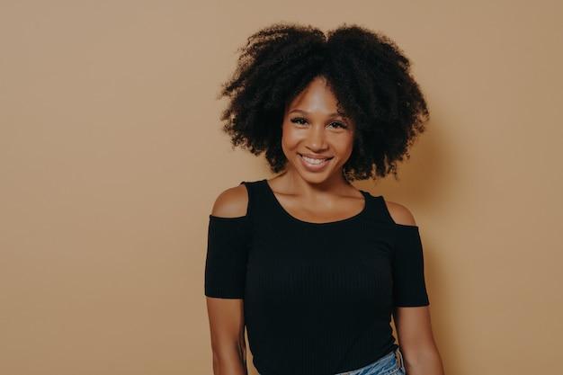 Uśmiechnięta afroamerykańska kobieta z kręconymi włosami stojąca na beżowym tle
