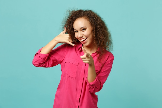 Uśmiechnięta afrykańska dziewczyna robi telefon gest jak mówi oddzwoń do mnie, wskazując palcem wskazującym na aparat na białym tle na niebieskim tle turkus. ludzie szczere emocje, koncepcja stylu życia. makieta miejsca na kopię.