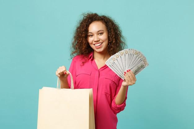Uśmiechnięta afrykańska dziewczyna trzymaj torbę z zakupami po zakupach, fan pieniędzy w banknotach dolara, gotówka na białym tle na niebieskim tle turkus. koncepcja życia ludzi. makieta miejsca na kopię.