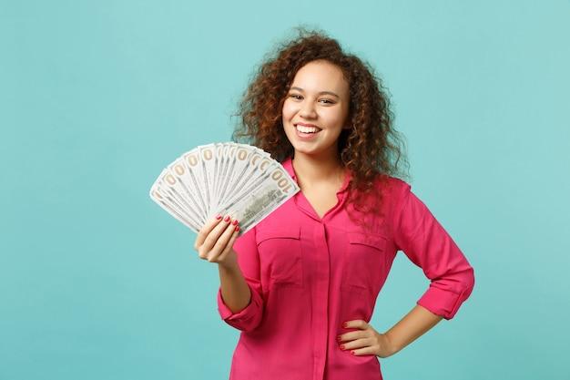 Uśmiechnięta afrykańska dziewczyna w ubranie trzyma fan pieniędzy w banknotach dolara, pieniądze na białym tle na tle niebieskiej ściany turkus. ludzie szczere emocje, koncepcja stylu życia. makieta miejsca na kopię.