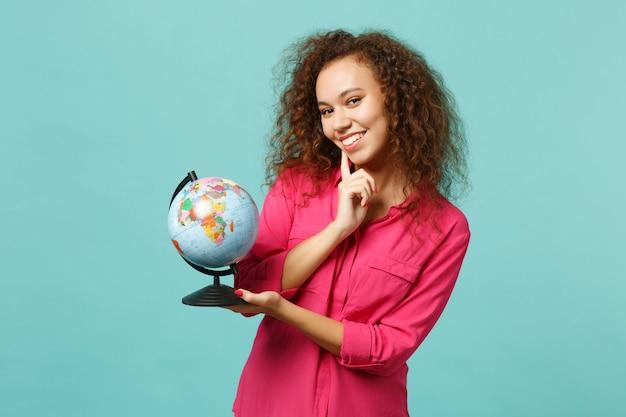 Uśmiechnięta afrykańska dziewczyna w zwykłych ubraniach trzymaj w rękach globus ziemi, podnieś rękę podpierając się na brodzie na białym tle na niebieskim turkusowym tle. ludzie szczere emocje, koncepcja stylu życia. makieta miejsca na kopię.