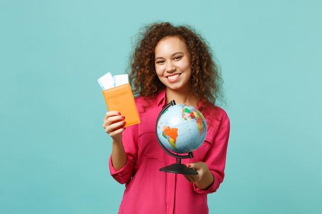 Uśmiechnięta afrykańska dziewczyna w zwykłych ubraniach trzymających kulę ziemską świata, paszport, bilet na kartę pokładową, na białym tle na niebieskim turkusowym tle. ludzie szczere emocje, koncepcja stylu życia. makieta miejsca na kopię.
