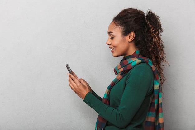 Uśmiechnięta afrykańska kobieta na sobie płaszcz stojący, przy użyciu telefonu komórkowego