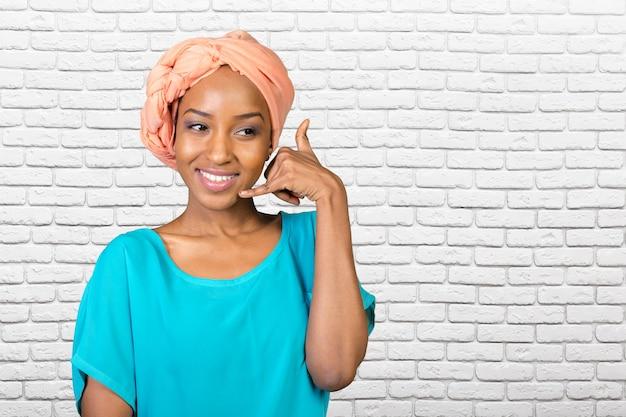 Uśmiechnięta afrykańska kobieta robi wezwaniu ja szyldowy