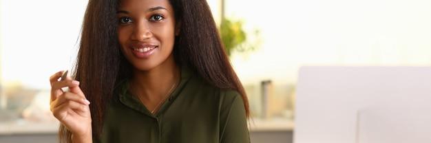 Uśmiechnięta afrykańska kobieta siedzi w biurze trzymając notebooki i pióro.