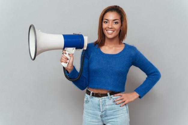 Uśmiechnięta afrykańska kobieta trzyma megafon w jednej ręce i drugiej na biodrze. na białym tle szarym tle