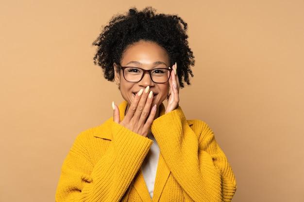 Uśmiechnięta afrykańska kobieta tysiąclecia nosić okulary patrząc na aparat ze śmiechem, zakryć usta ręką